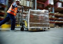 man pushing cart in a trading warehouse.