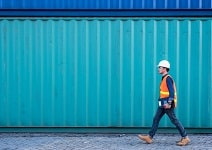 man walking past containers.