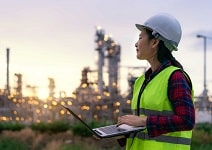 woman petrochemical engineer working at night with laptop Inside oil and gas refinery plant